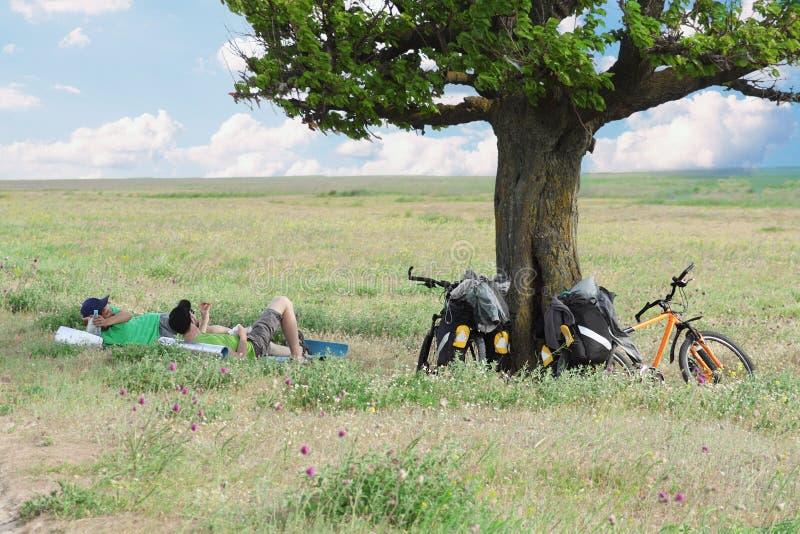 Turistas da bicicleta que descansam perto da árvore fotografia de stock royalty free