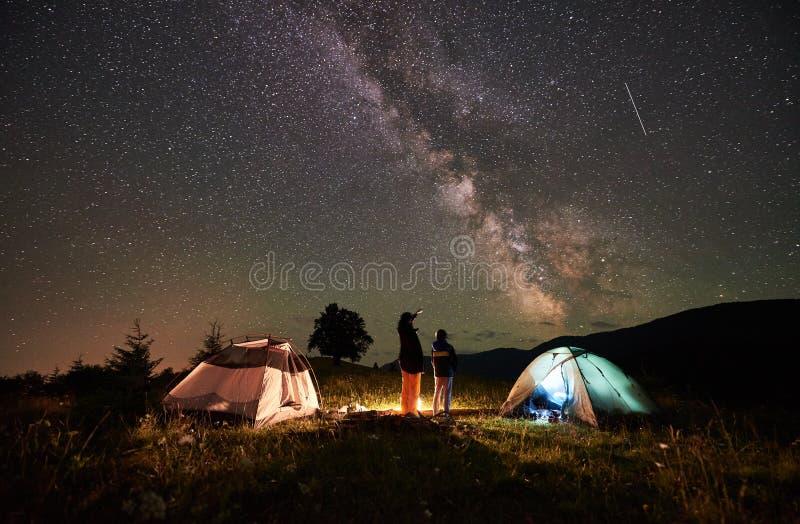 Turistas da mãe e do filho que descansam no acampamento nas montanhas no céu noturno completamente das estrelas e da Via Látea imagens de stock