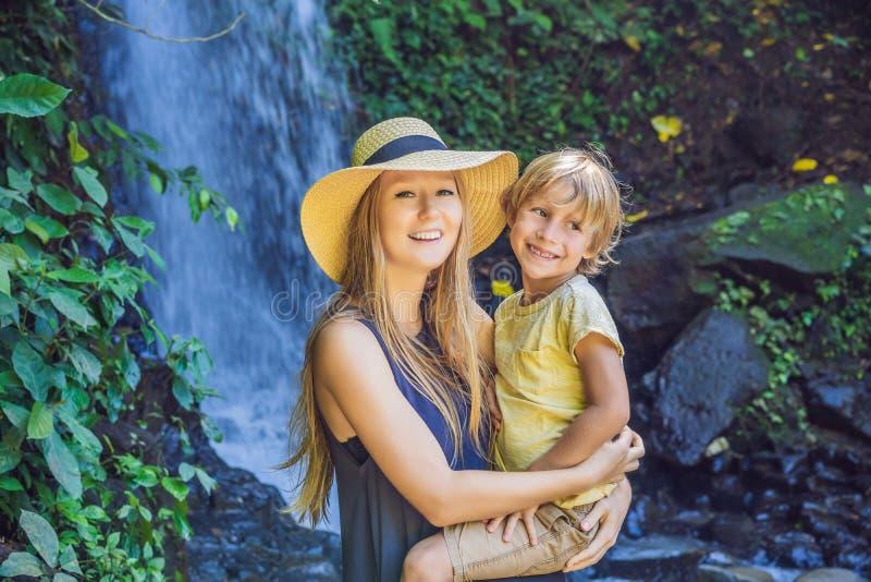 Turistas da mamã e do filho no fundo de uma cachoeira Viagem com conceito das crian?as Que a fazer com crianças das crianças fotografia de stock