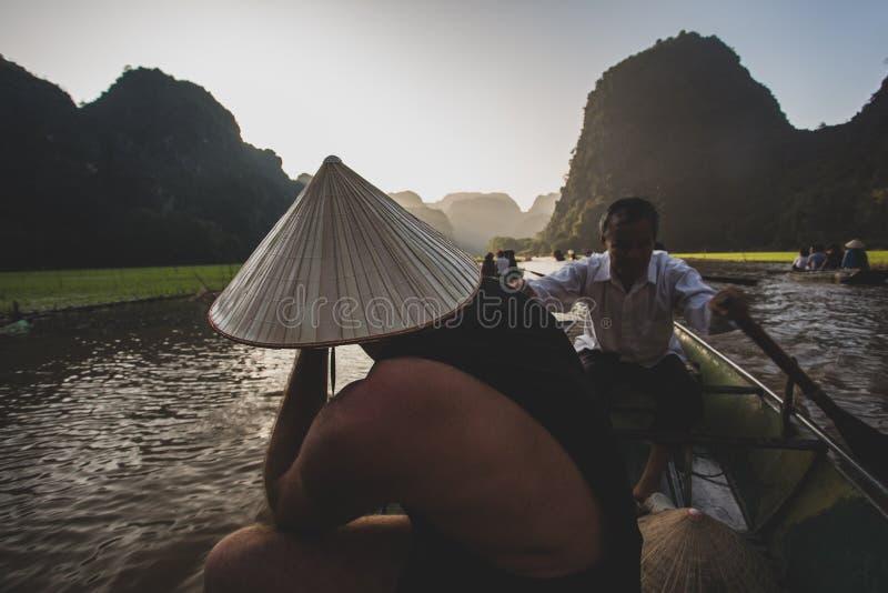 Turistas das balsas de um barqueiro ao longo da ba?a de Halong na atra??o tur?stica da terra em Tam Coc, Vietname foto de stock royalty free