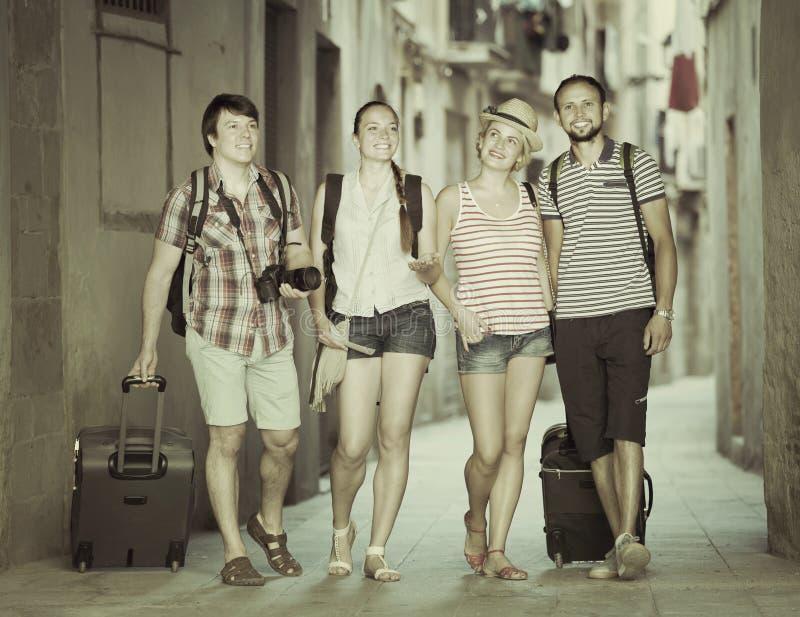 Turistas de Hppy en la calle con equipaje imagen de archivo libre de regalías