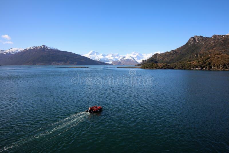 Turistas de la aventura en un zodiaco de Ventus australis en la bah?a de Ainsworth en Patagonia chile foto de archivo