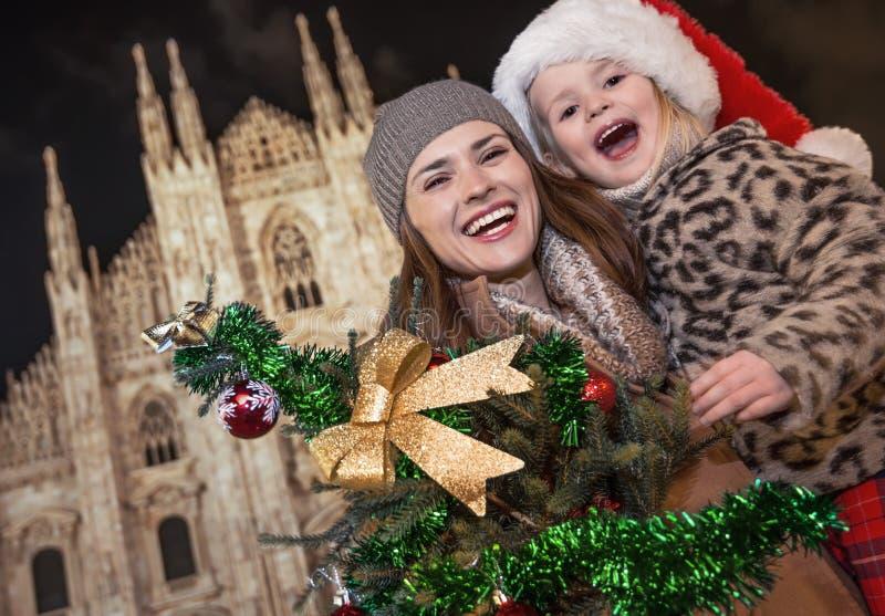 Turistas de la madre y de la hija que muestran el árbol de navidad en Milán fotos de archivo
