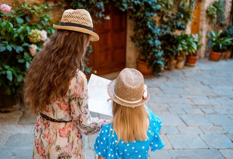 Turistas de la madre y de la hija en la ciudad italiana vieja que mira el mapa fotografía de archivo libre de regalías