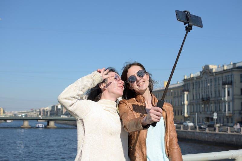 Turistas de las se?oras jovenes en selfies de la toma de St Petersburg Rusia en un puente de madera en el centro de ciudad hist?r foto de archivo libre de regalías