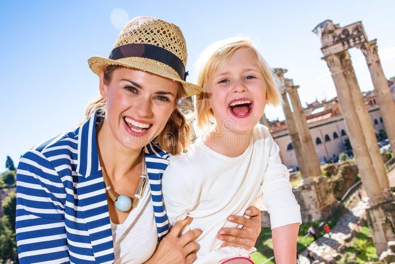 Turistas de sorriso da mãe e da filha na frente de Roman Forum imagens de stock royalty free