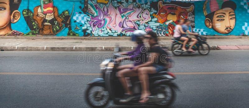 Turistas de Tailândia no 'trotinette' contra a parede dos grafittis foto de stock