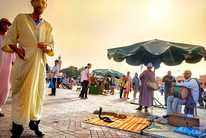 Turistas del entertein de los encantadores y de los músicos de serpientes en mercado del EL Fna de Djemaa Marrakesh, Marruecos foto de archivo libre de regalías