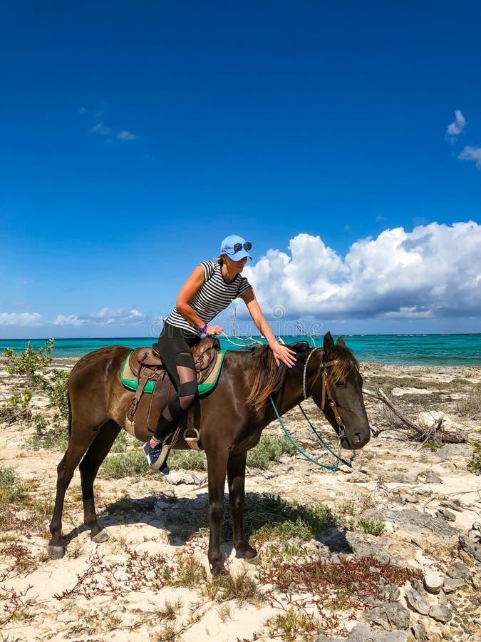 Turistas del montar a caballo en Cuba Muchacha en un caballo en una playa foto de archivo