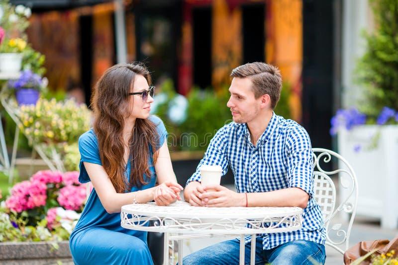Turistas del restaurante que comen en el café al aire libre Los amigos jovenes disfrutan del tiempo junto en día de verano foto de archivo