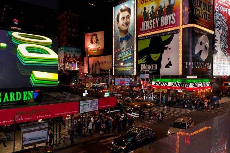 Turistas del Times Square de NYC en la noche imagenes de archivo