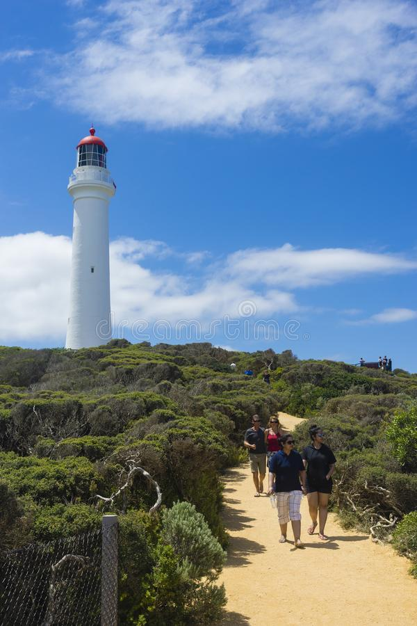 Turistas e farol rachado na grande estrada do oceano, Austrália do ponto fotografia de stock