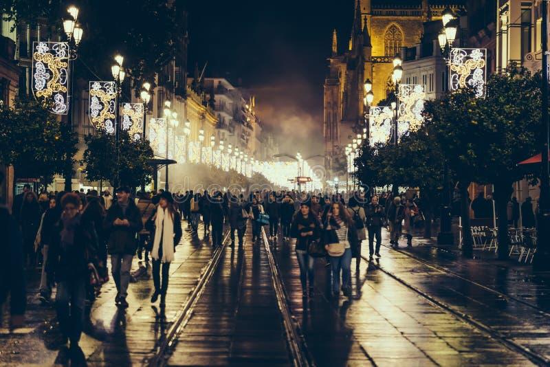 Turistas e povos que andam na noite de Natal no centro histórico de Sevilha, Espanha imagem de stock