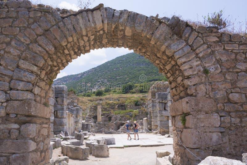 Turistas em ruínas velhas da cidade antiga de Ephesus no dia ensolarado, Izmir, Turquia Marco famoso do turco foto de stock