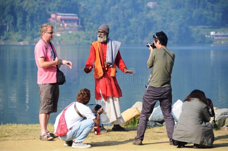 Turistas em torno de um encantador de serpente em Nepal fotografia de stock royalty free
