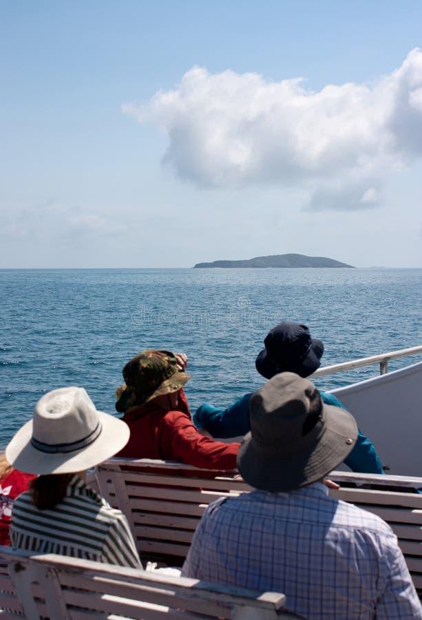 Turistas em um barco em um cruzeiro que olha uma ilha em uma distância na maneira à grande ilha de Keppel na área do Capricórnio  fotografia de stock