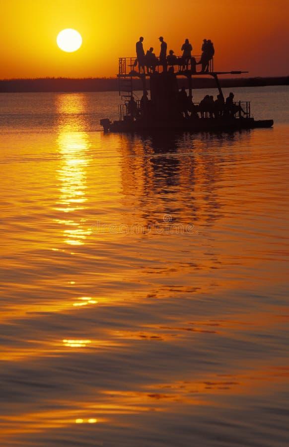 Turistas em um barco no por do sol, Botswana foto de stock royalty free