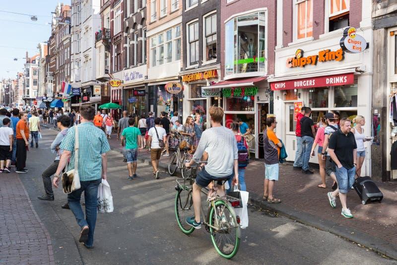 Turistas en Amsterdam que hacen compras y que buscan un restaurante fotos de archivo