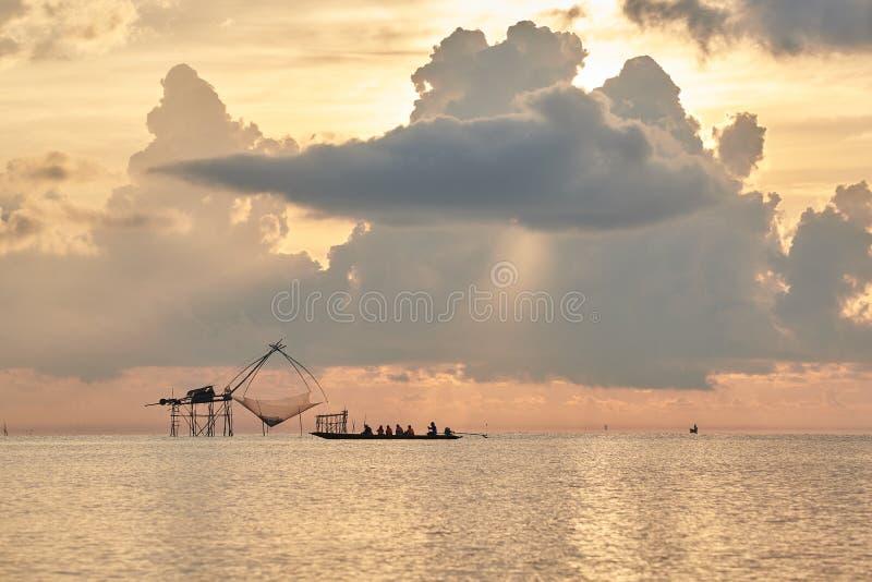Turistas en el barco de la cola larga que toma fotografía de la pesca neta durante salida del sol por la mañana foto de archivo