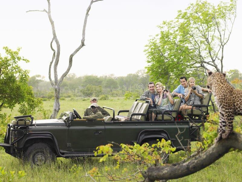 Turistas en el registro de Jeep Looking At Cheetah On imagen de archivo libre de regalías