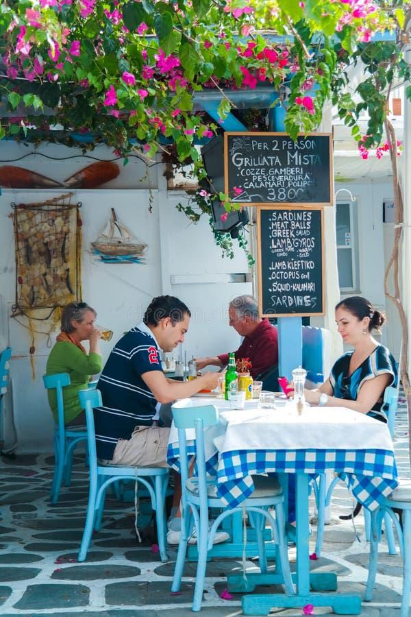 Turistas en el restaurante en la playa cerca del molino de viento famoso cuatro imagen de archivo libre de regalías