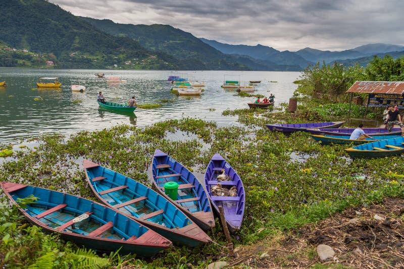 Turistas en el símbolo del bote de remos de la orilla del lago de Phewa en Pokhara imagen de archivo