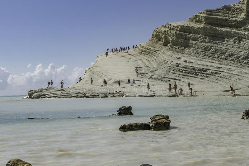 Turistas en la costa costa de la piedra caliza con la vista escénica del océano azul cristal en pasos de los turcos en Sicilia en imagenes de archivo