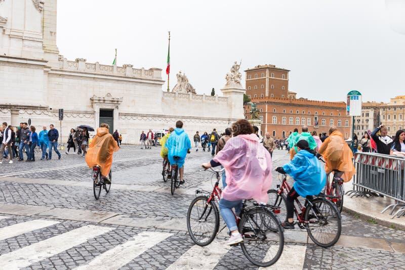 Turistas en las bicicletas en un día lluvioso en el centro de Roma fotografía de archivo