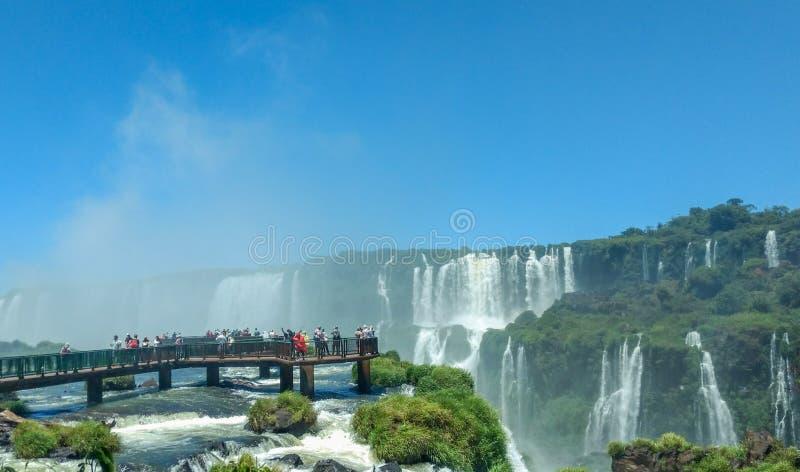 Turistas en las cataratas del Iguazú, una maravillas naturales del ` s del mundo de las grandes, en la frontera del Brasil y de l fotografía de archivo libre de regalías