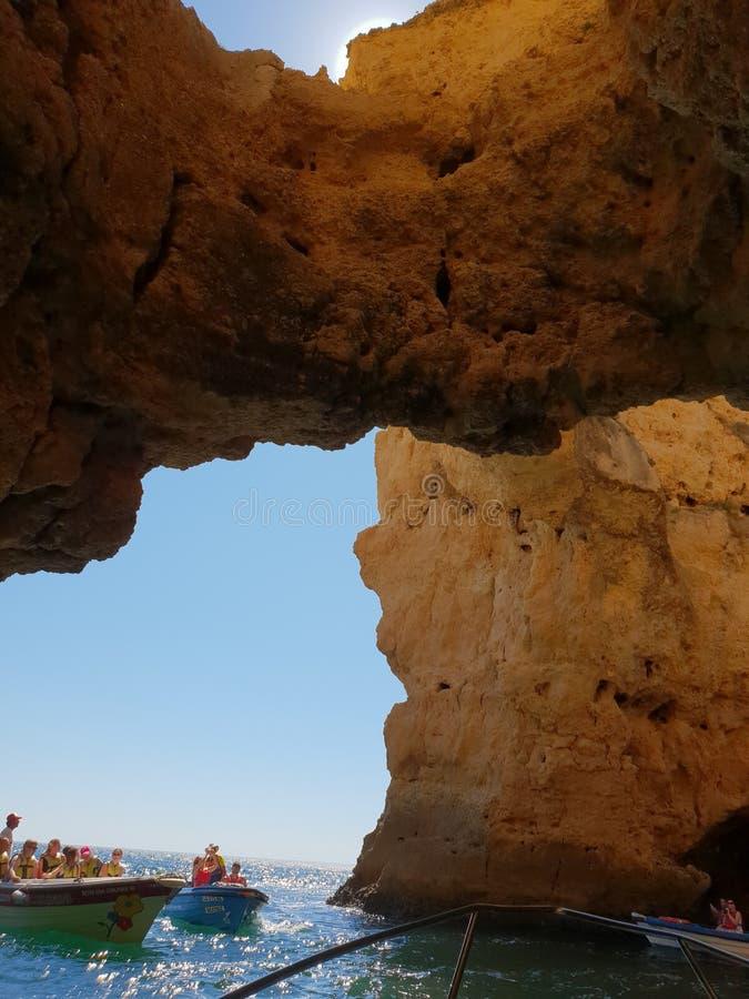 Turistas en los botes pequeños que exploran las muchas cuevas y gruta punteadas alrededor de la costa de Lagos, Portugal fotografía de archivo