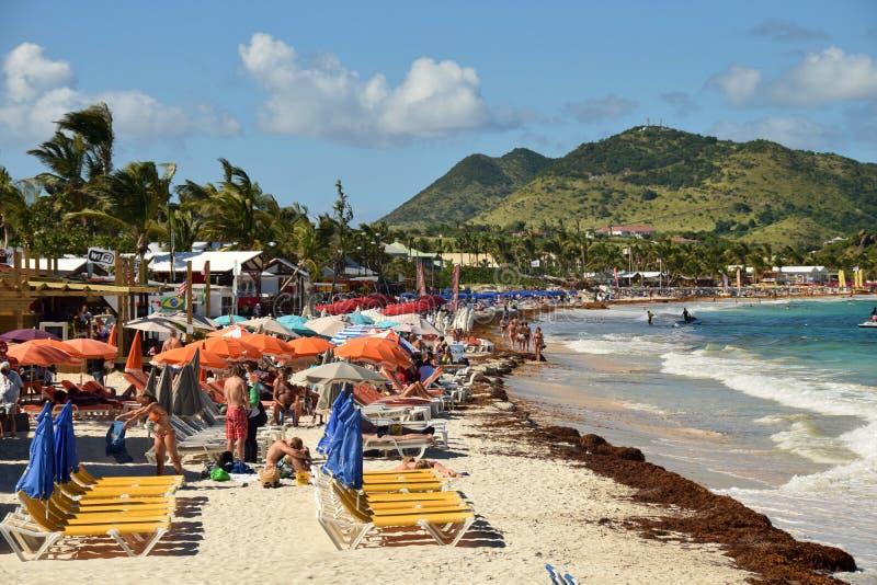 Turistas en St Maarten de la playa de Oriente foto de archivo
