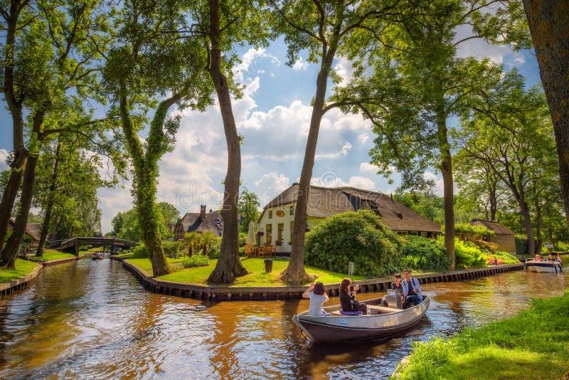 Turistas en un barco de visita turístico de excursión en el pueblo de Giethoorn, Países Bajos imagen de archivo libre de regalías