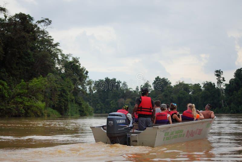 Turistas en un safari en el paseo de la selvaen el barco imágenes de archivo libres de regalías