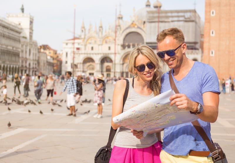Turistas en Venecia que mira el mapa de la ciudad imágenes de archivo libres de regalías