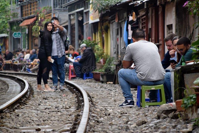 Turistas en y al lado de las pistas ferroviarias que corren el estrecho al lado de casas en Hanoi fotos de archivo