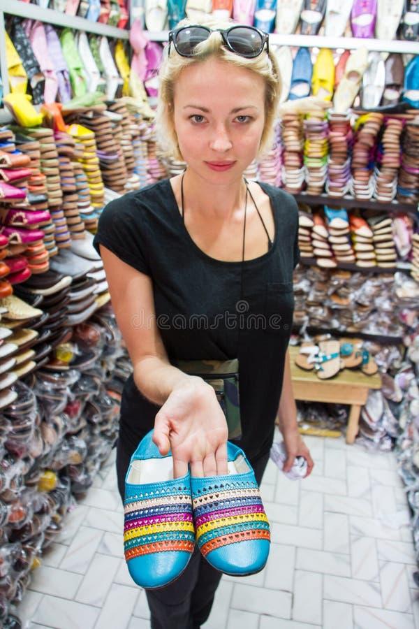Turistas fêmeas que olham sapatas de couro coloridas árabes tradicionais no mercado de compra da tenda de medina ao viajar foto de stock