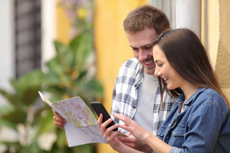 Turistas felices que comprueban el mapa y el teléfono de vacaciones imagen de archivo