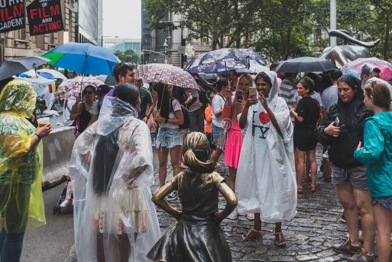 Turistas felices que toman las fotos con la estatua audaz de la muchacha en Manhattan más baja, en un día lluvioso fotos de archivo