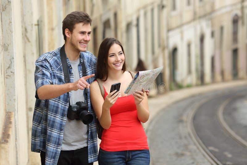 Turistas felizes que sightseeing em uma rua velha da cidade fotografia de stock