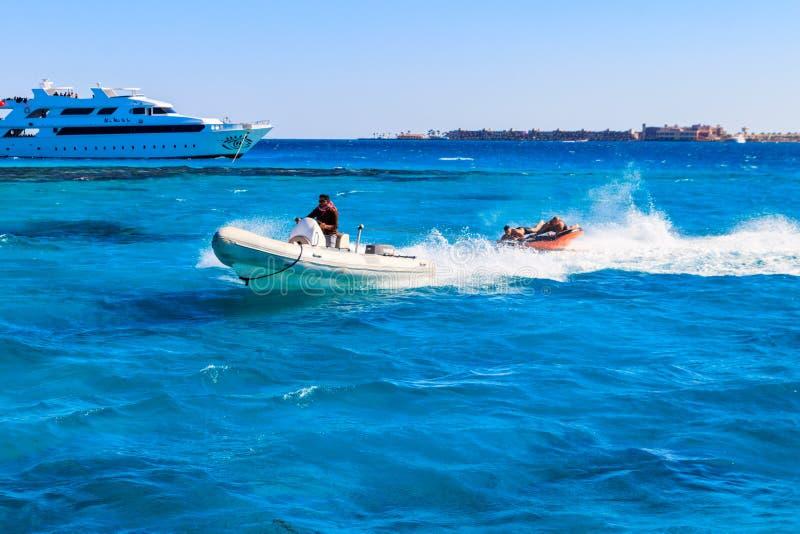 Turistas felizes que têm o divertimento que monta o barco inflável no Mar Vermelho fotografia de stock royalty free