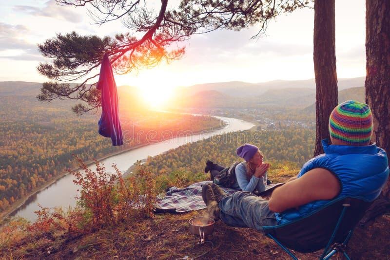 Turistas jovenes, caminante que se sienta en el top de las montañas de la colina y que mira puesta del sol hermosa del verano Par fotografía de archivo libre de regalías