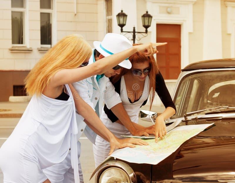 Turistas jovenes con un mapa de camino contra el coche retro imágenes de archivo libres de regalías