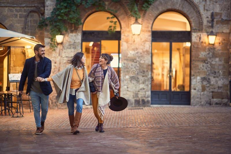 Turistas jovenes de los amigos que caminan alrededor de ciudad vieja de vacaciones imagenes de archivo
