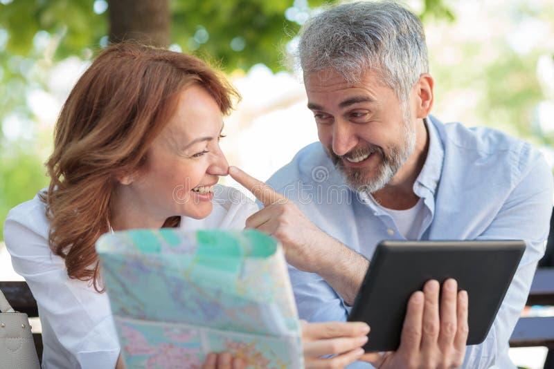 Turistas maduros juguetones que se sientan en un banco, trabajando en una tableta y mirando el mapa de la ciudad imagen de archivo libre de regalías