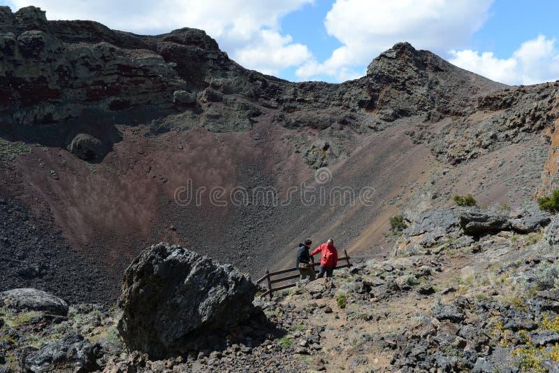 Turistas na cratera de um vulcão extinto no parque nacional Pali Aike no sul do Chile fotografia de stock royalty free