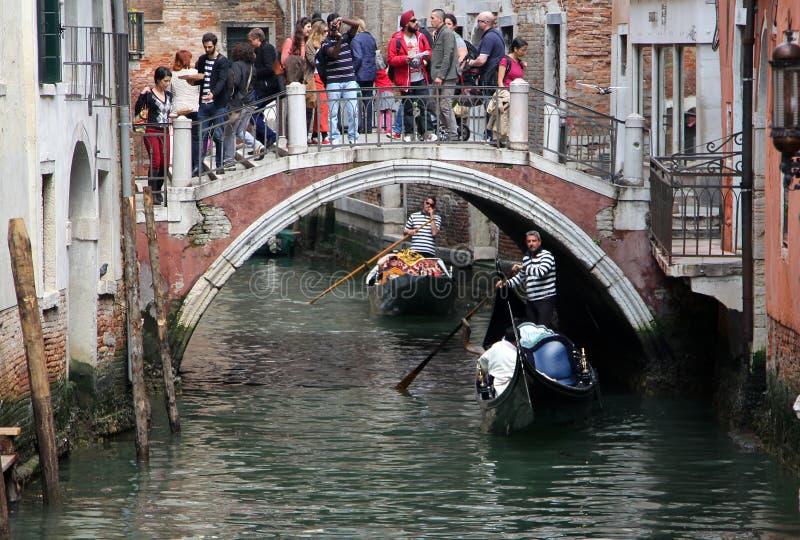 Turistas na ponte que olham as gôndola flutuar no canal fotos de stock