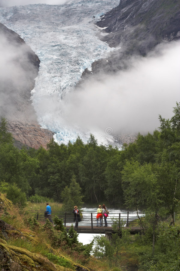 Turistas na ponte sobre o córrego na geleira de Briksdal fotografia de stock royalty free
