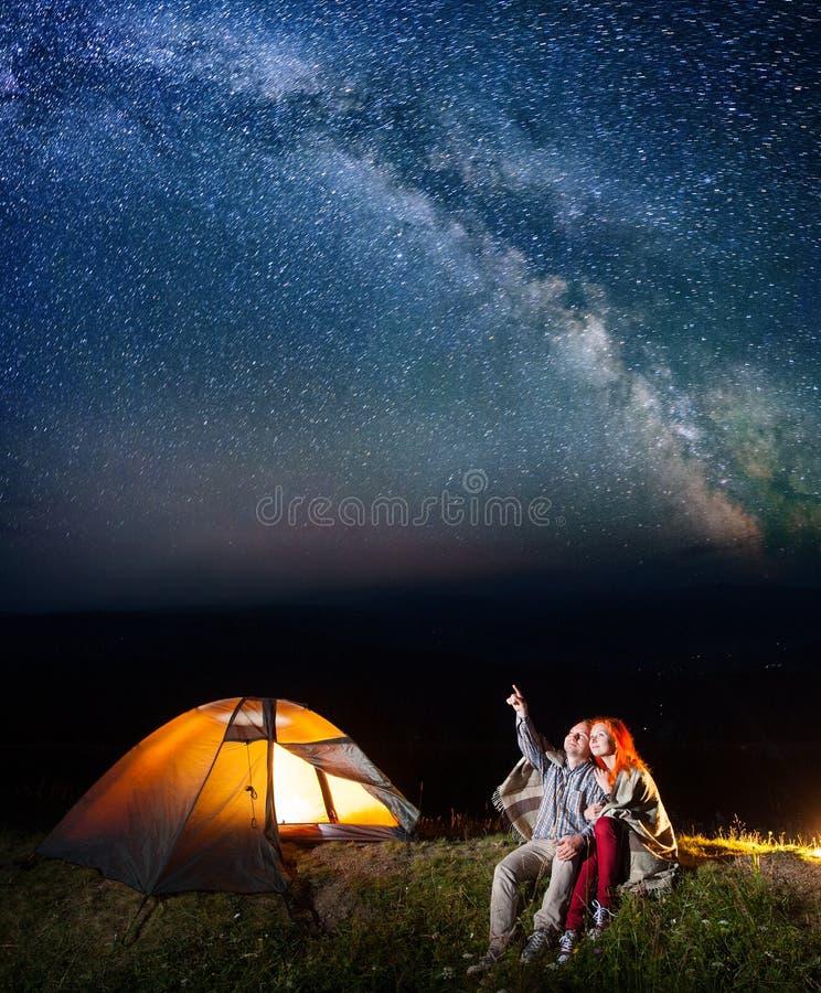 Turistas no acampamento na noite contra o céu estrelado fotografia de stock