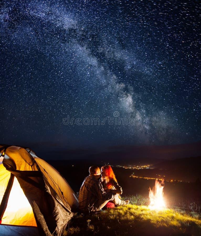 Turistas no acampamento na noite contra o céu estrelado imagem de stock royalty free