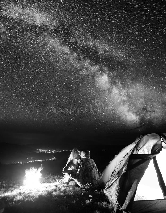 Turistas no acampamento na noite contra o céu estrelado foto de stock